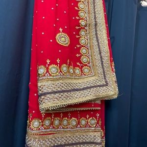 Carrot Red Saree with heavy work on it.